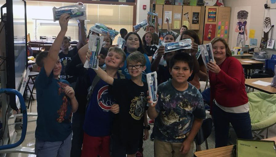 Classroom of students with dental health care packages