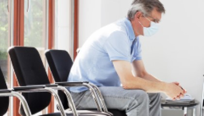 Man sitting on chair in waiting room.