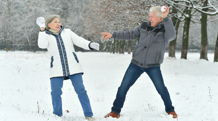 Two older adults playing in the snow.
