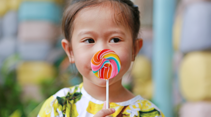 Child holding a lollipop.