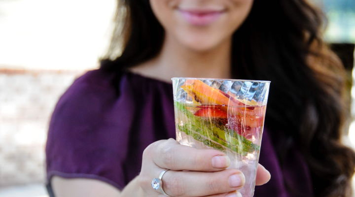 Woman holding a sugar-free summer drink with fruit in it.